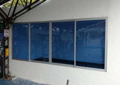 Ventana corrediza sistema 744 aluminio natural y vidrio azul
